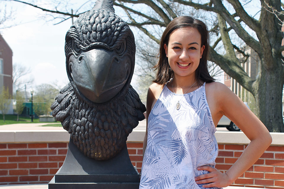 Maria Castiblanco stands next to Reggie Redbird's bust in Redbird Plaza.